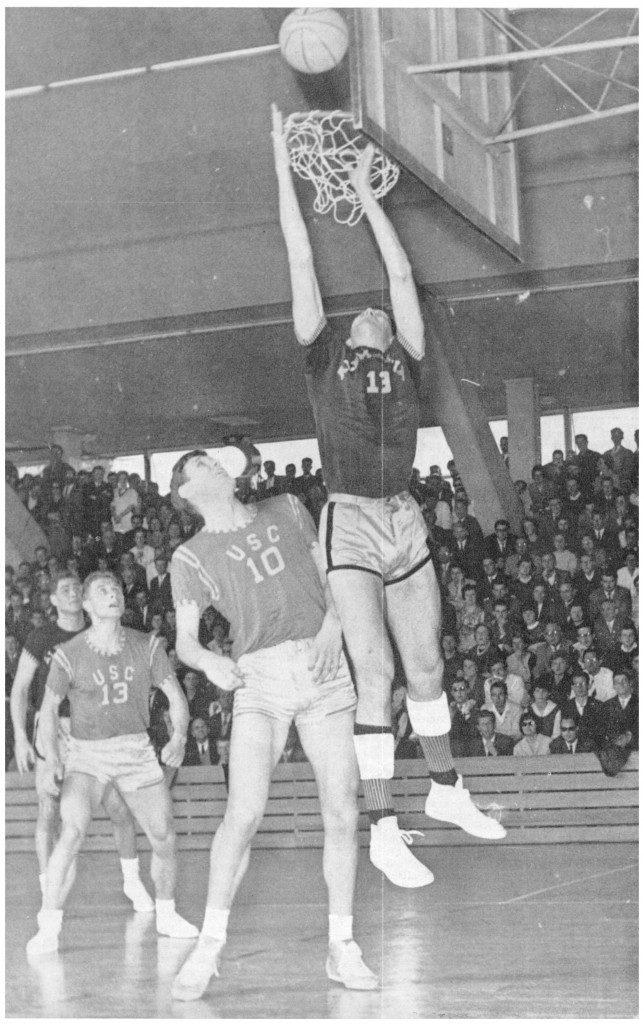 """Die Endspielszene zeigt vor stattlicher Kulisse in der Wiesbadener Sporthalle den Aachener John Loridon am Brett, dahinter die Heidelberger Klaus Weinand (10) und Volker Heindel (13) (Foto: Oertel, Quelle: """"Basketball"""", Ausgabe v. 24. Mai 1962)."""